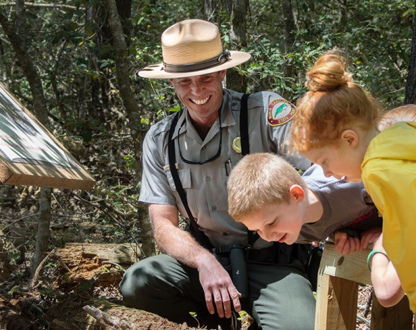 Ranger Jamie Cameron invites youngsters to touch and smell a rotten log on the Holly Discovery Trail.