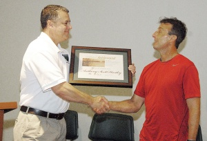 Scott Hartley, right, accepts retirement plaque from Mike Lambert, chief of operations.