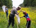 Interpreter Brian Bockhahn helps a young volunteer identify an insect during a Monarch butterfly tagging program at Falls Lake.