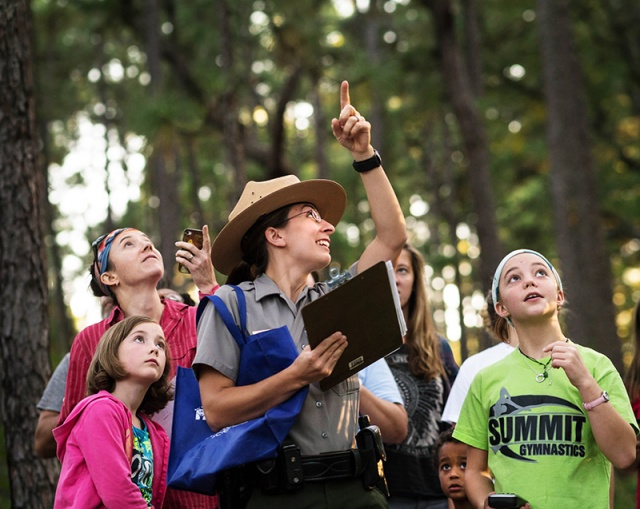 Ranger Nancy Williamson points out the sound of a red cockaded woodpecker during a GPS navigation program at Weymouth Woods State Historic Preserve.