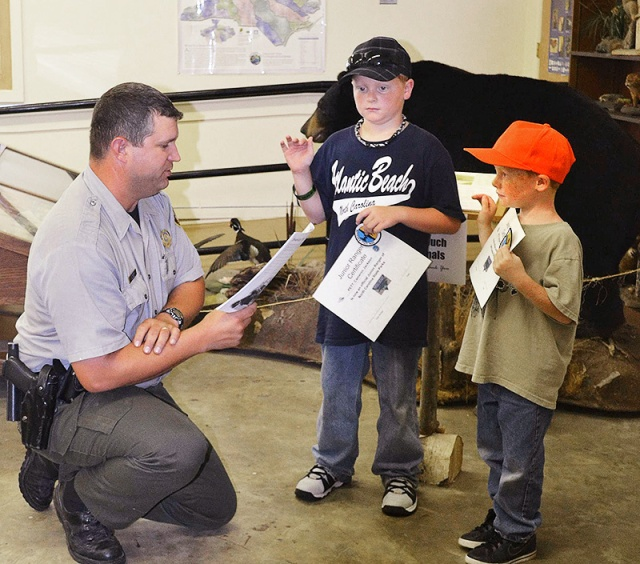 Ranger Steve Rogers swears in Cameron and Christian Webb as Junior Rangers at Pettigrew State Park.