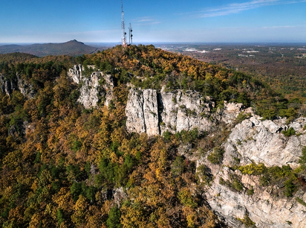Aerial view shows Crowders Mountain summit with The Pinnacle in the background, both within Crowders Mountain State Park.