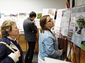 Visitors examine designs from seven university teams for a state park visitor center.