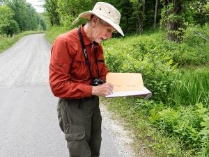A researcher catalogues plant species along the park road.