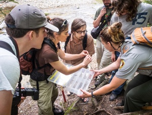 Researchers and students examine a crayfish found in a park stream.