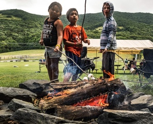 Kids from different families meet over the campfire.